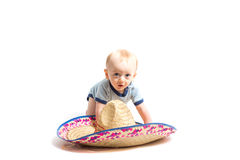 Baby and Sombrero on White. A 6 month old baby crawling towards a sombrero hat on a white studio floor Stock Photo