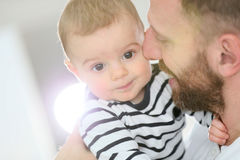 Baby son in the arms of his father cuddling. Portrait of daddy embracing baby boy Royalty Free Stock Photography
