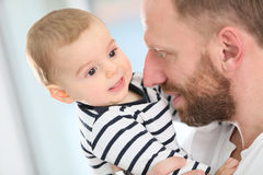 Baby son in the arms of his father. Portrait of daddy embracing baby boy Stock Images
