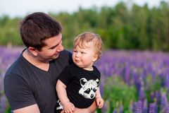 Baby son with dad in lupine field Royalty Free Stock Images