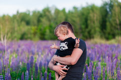 Baby son with dad in lupine field. With trees on background Stock Photos