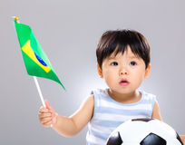 Baby son holding flag amd soccer ball. Baby son holding flag and soccer ball with gray background Stock Image