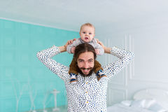Baby son sitting on father neck in white room Stock Photo