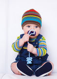 Baby with soother. Sitting on the sofa royalty free stock photos