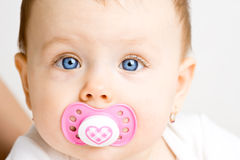 Baby with soother. Frontal view of a cute baby girl with a soother in her mouth Royalty Free Stock Photos