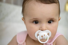 Baby with soother. Baby girl with white soother stock photo