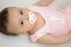 Baby with soother. Baby girl with white soother royalty free stock images