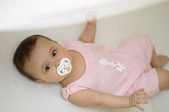 Baby with soother. Baby girl with white soother royalty free stock photography