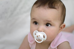 Baby with soother. Baby girl with white soother Royalty Free Stock Photos