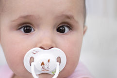 Baby with soother. Baby girl with white soother Stock Image