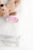 Baby soother and laundry. Baby soother and teddy bear on fresh laundry Stock Images