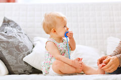 Baby with soother looking on mother Stock Image