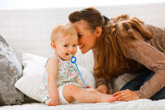 Baby with soother and mother playing on divan Stock Images