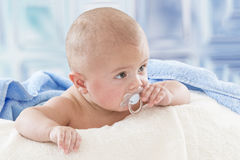 Baby with soother in the mouth a towel after bath royalty free stock photography