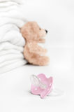 Baby soother and teddy. Baby soother with teddy and laundry in background Royalty Free Stock Photo