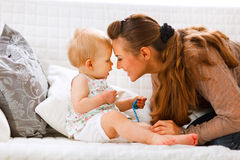 Baby with soother and young mom playing on divan. Cute baby with soother and young mom playing on divan at home Royalty Free Stock Image