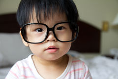 Baby in spectacles. Portrait of a baby girl wearing big spectacles Stock Photo