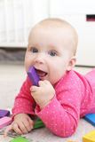 Baby spielt hölzernes mehrfarbiges meccano zu Hause Stockfotografie