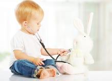 Baby spielt im Doktorspielzeughäschen und -stethoskop Stockfoto