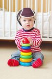 Baby spielt zu Hause im Babyschutzhelm Stockbild