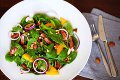 Baby spinach salad with sweet mango, almonds and toasted ham Royalty Free Stock Image