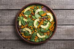 Baby spinach salad with sweet potato , chickpeas and avocado . Vegan healthy food royalty free stock images
