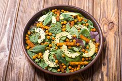 Baby spinach salad with sweet potato , chickpeas and avocado . Vegan healthy food royalty free stock photo