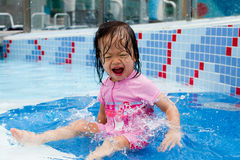 Baby Splashing At Pool. Little asian baby splashing at a wading pool royalty free stock photos
