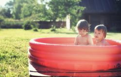 Baby splashing in the pool outdoors. Cute little kids on nature in summer on the site in a country house Royalty Free Stock Images