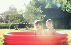 Baby splashing in the pool outdoors. Cute little kids on nature in summer on the site in a country house Royalty Free Stock Photos