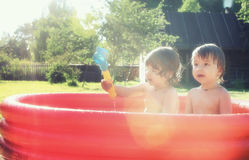 Baby splashing in the pool outdoors. Cute little kids on nature in summer on the site in a country house Stock Images