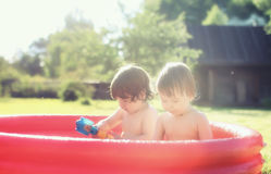 Baby splashing in the pool outdoors. Two small children bathe in a bathroom installed on the lawn in nature summer day Stock Image