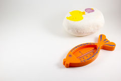 Baby sponge body and a thermometer for water on a white backgrou Stock Image