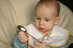The baby and the spoon. The kid of 6 months sits with the spoon Royalty Free Stock Photos