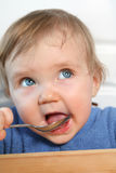 Baby with a spoon. Adorable blue eyed baby eating from a spoon Stock Photo