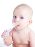 Baby with spoon. Baby girl holding spoon in mouth Stock Photography