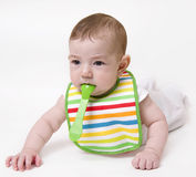 Baby with spoon in mouth looking aside.  Stock Image