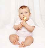 Baby with spoon sitting on the bed Stock Photos