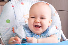 Baby with spoon, smiling Royalty Free Stock Photo