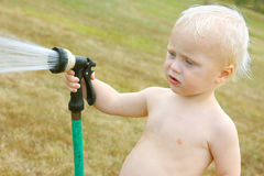 Baby Spraying Garden Hose Stock Photos