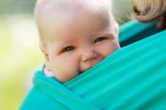 Baby stängde sig till mamman i rem royaltyfri fotografi