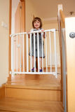Baby and the stair gate Stock Photography