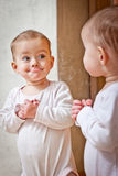 Baby standing against the mirror. Little Baby standing against the mirror and looking at the reflection Royalty Free Stock Photography