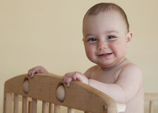 Baby standing in cot. Baby with a cute happy face standing in a cot Stock Photos