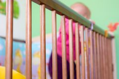 Baby standing in a crib and holding side of the bed. Royalty Free Stock Photo
