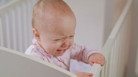 Baby Standing in a Crib at Home. Crying. Baby`s standing in a white crib at home and crying. Close-up shot Royalty Free Stock Photography