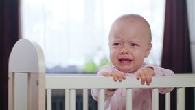 Baby Standing in a Crib at Home. Crying. Baby`s standing in a white crib at home and crying. Medium shot Stock Photo