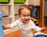 Baby standing on his feet in the children's room and smiling Stock Images
