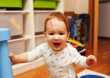 Baby standing on his feet in the children's room and smiling Royalty Free Stock Photography