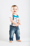 Baby Standing Holding Hands and Smiling. A cute 1 year old stands in a white studio setting. The boy has a happy expression. He is dressed in Tshirt, jeans Stock Image